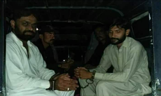 The culprits arrested by the police sit in the police vehicle.